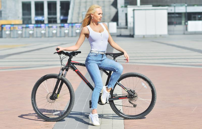 Sexy girl with perfect body on black bike. Beautiful sunrise in the forest. nature background, woman, young, cute, beauty, sport, white, healthy, bicycle royalty free stock photography