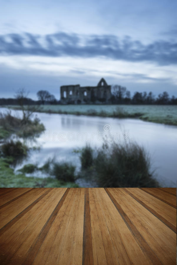 Beautiful sunrise landscape of Priory ruins in countryside location with wooden planks floor royalty free stock photos