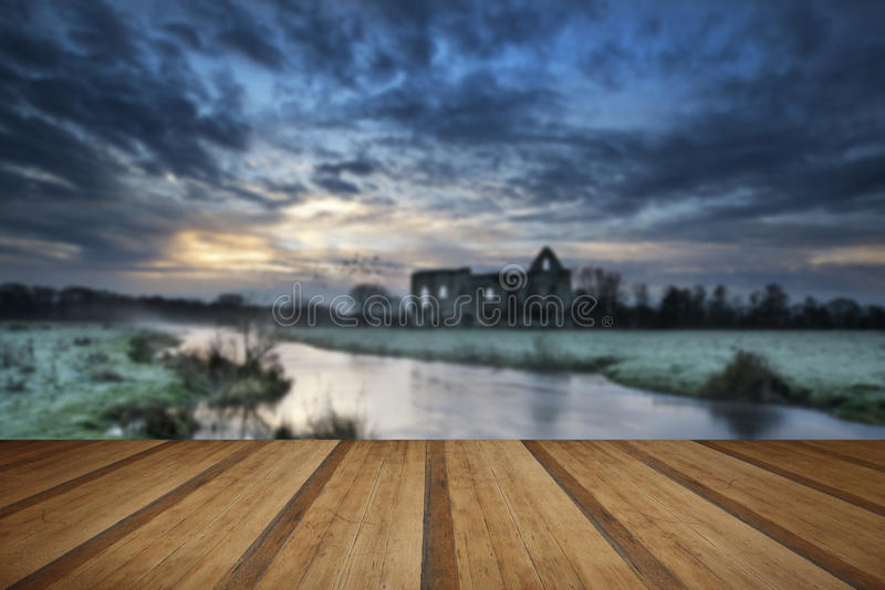 Beautiful sunrise landscape of Priory ruins in countryside location with wooden planks floor stock image