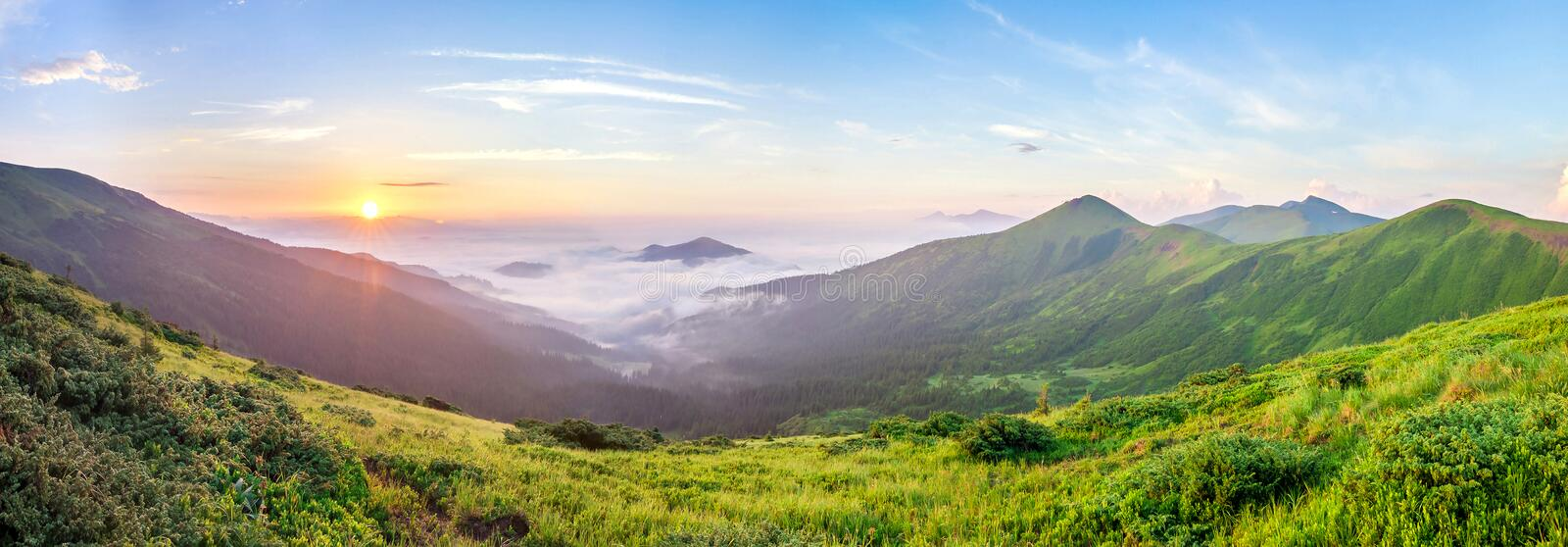 Beautiful sunrise in mountains with white fog below panorama royalty free stock photography