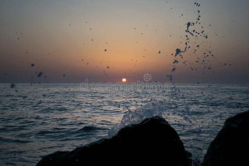 A beautiful sunrise on the ocean. Boat and rocks near the shore. waves that hit the stones and water is scattered royalty free stock photos