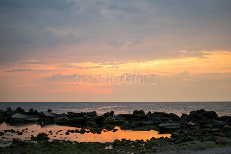 A beautiful sunrise on the ocean. Reflexions of the sun in water. rocks near the shore. A beautiful sunrise on the ocean. Boat and rocks near the shore stock photos