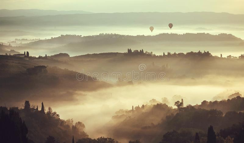 Beautiful sunrise over hills in Tuscany with garden trees, mansions, green hills. Fog in Italian countryside royalty free stock photo