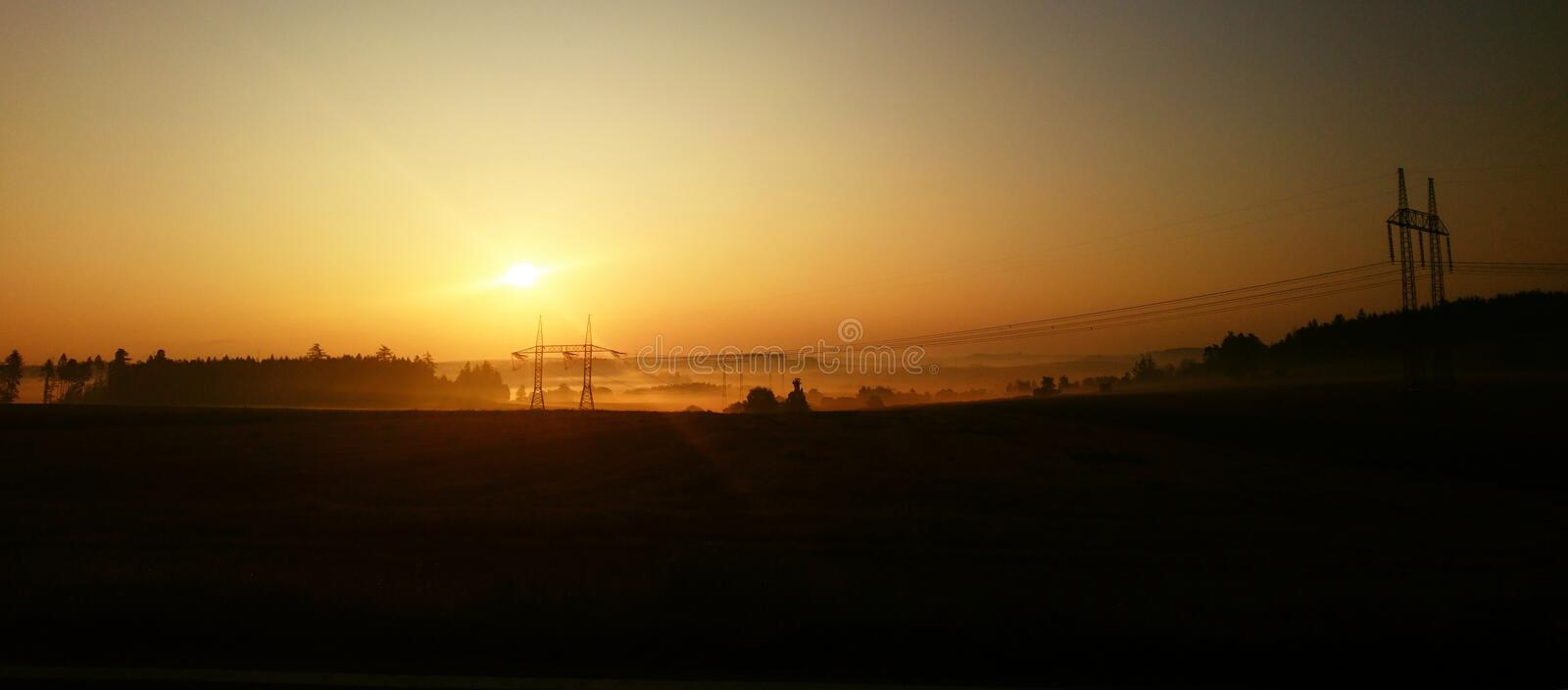 Beautiful Sunrise over Landscape with Electricity Pylons stock photography