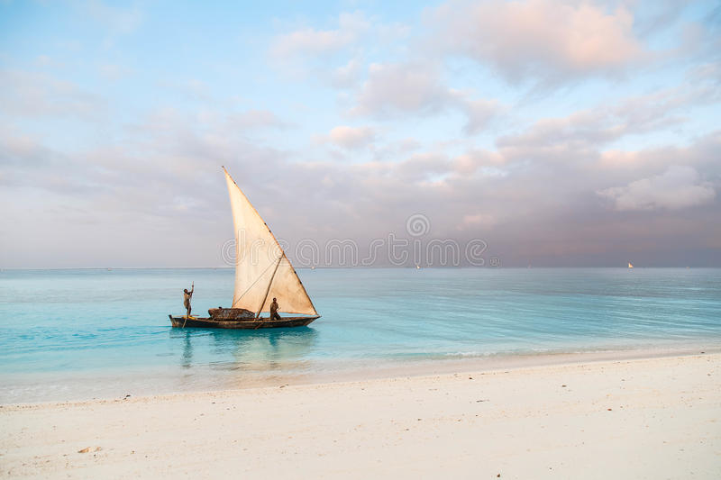 Beautiful sunrise over ocean with fishing boat, fishermen, Nungwi, Kendwa, Zanzibar island, Tanzania stock photography