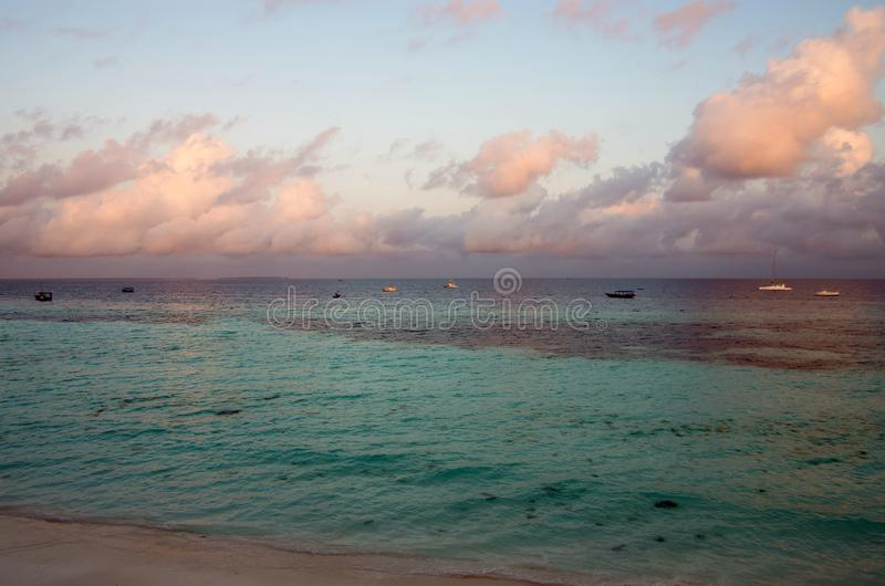 A beautiful sunrise over the ocean with yachts in the north of Zanzibar royalty free stock photo