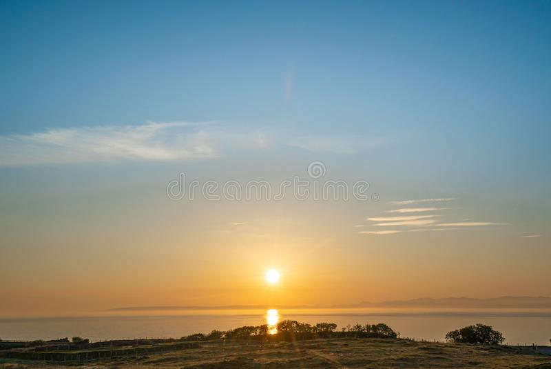 Beautiful Sunrise over the sea with light shining over the water surface reflecting golden. royalty free stock images