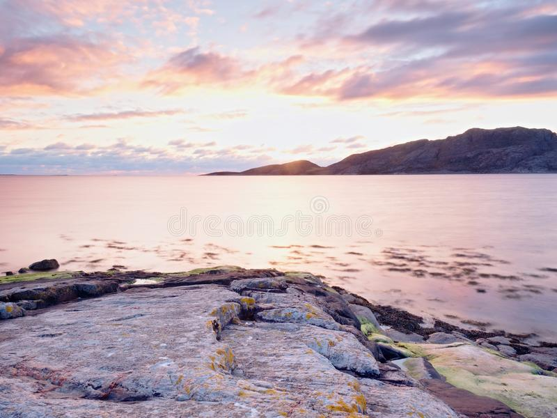 Beautiful sunrise on rocky shore and dramatic sky clouds. royalty free stock image