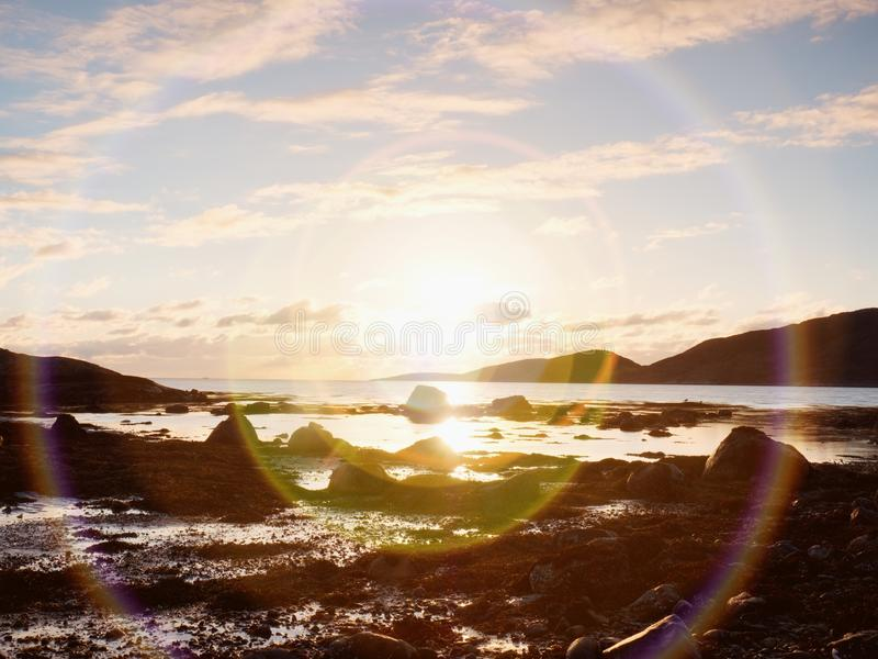 Beautiful sunrise on rocky shore and dramatic sky clouds. stock photo