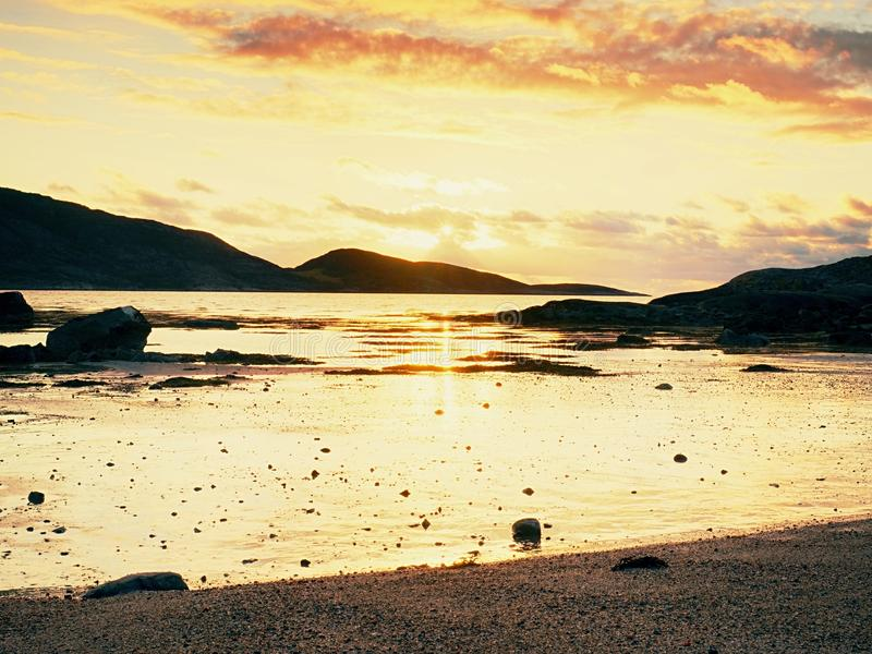 Beautiful sunrise on rocky shore and dramatic sky clouds. royalty free stock images