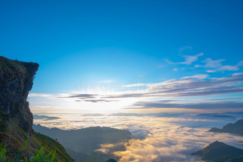 \'Beautiful sunrise scene at high mountain with yellow clouds and blue sky, Phu chi fah Chiangrai Thailand I. \'Beautiful sunrise scene at high mountain with stock photo