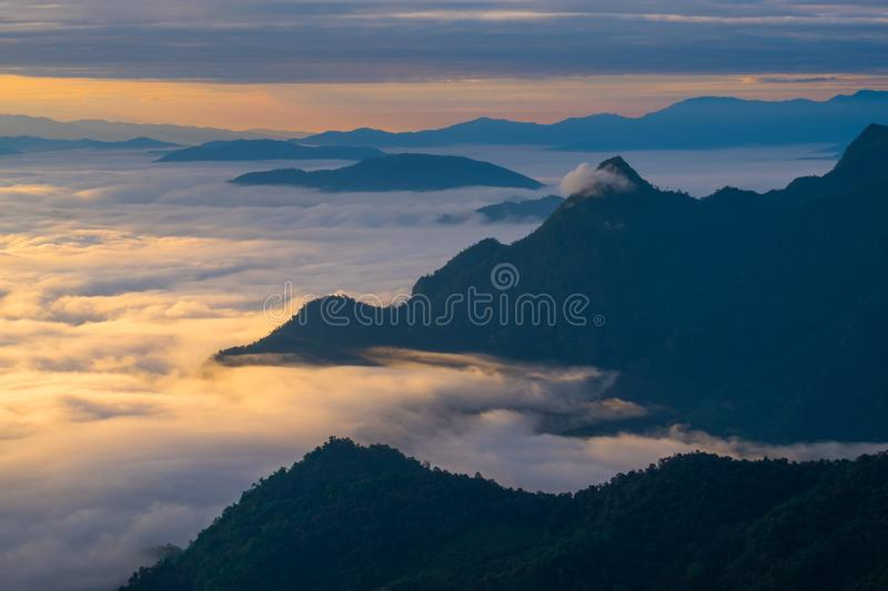 \'Beautiful sunrise scene at high mountain with yellow clouds and blue sky, Phu chi fah Chiangrai Thailand I. \'Beautiful sunrise scene at high mountain with royalty free stock photo