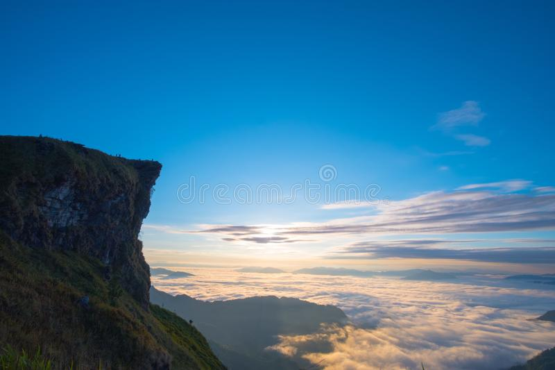\'Beautiful sunrise scene at high mountain with yellow clouds and blue sky, Phu chi fah Chiangrai Thailand I. \'Beautiful sunrise scene at high mountain with stock image