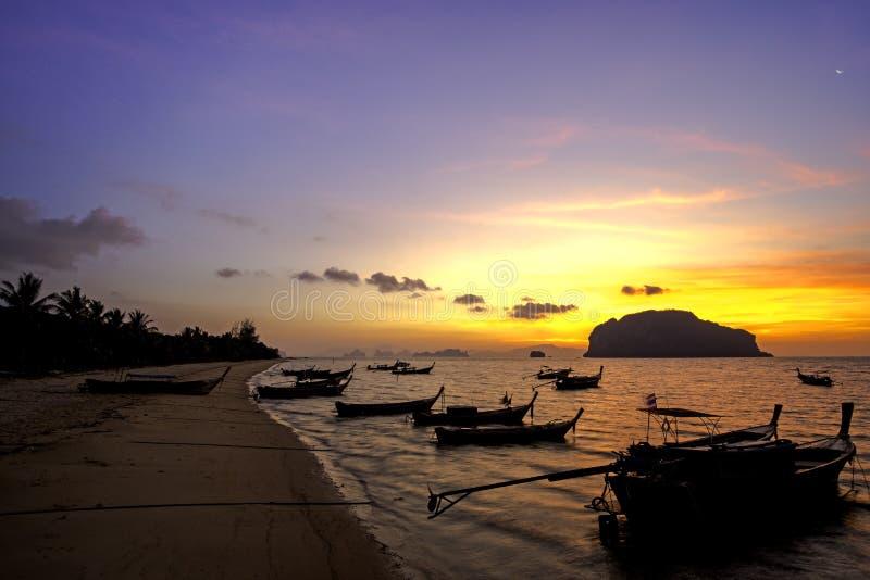 Beautiful sunrise scene at local beach and fisherman boat on small island stock photos