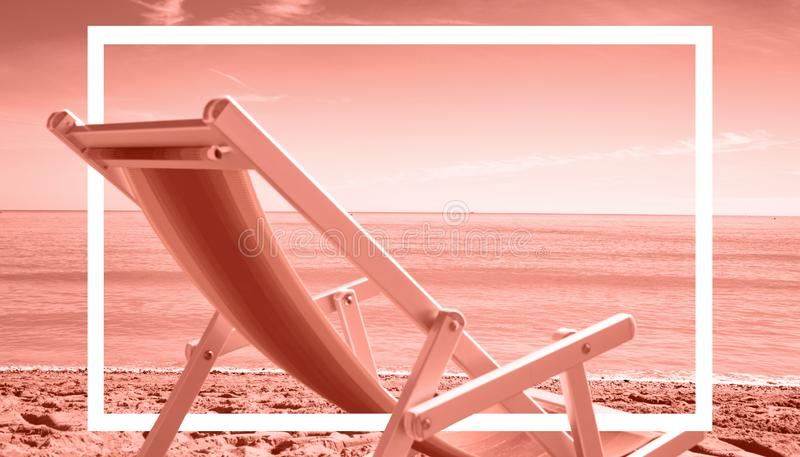 Beautiful sunrise at the sea with deck chair on the beach royalty free stock photography