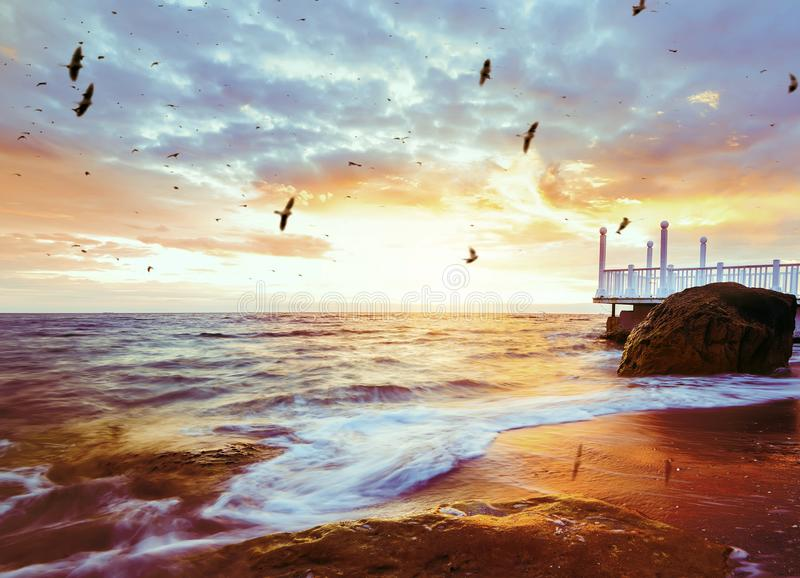 Beautiful sunrise by the sea. Wooden cozy pier on the shore and the rising sun. royalty free stock image