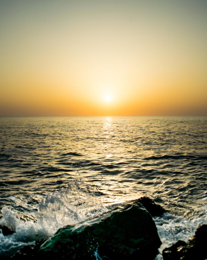 A beautiful sunrise on the seashore. the waves of the sea hit the rocks scattering water. the sun is making its appearance in a stock image