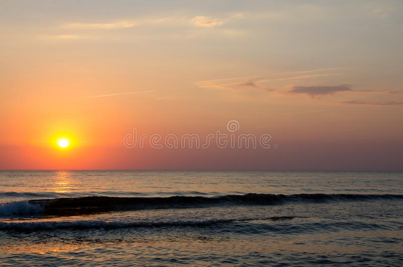 Beautiful sunrise and sunset with clouds over horizon blue sea background in morning and evening. Scenic seascape with golden royalty free stock images