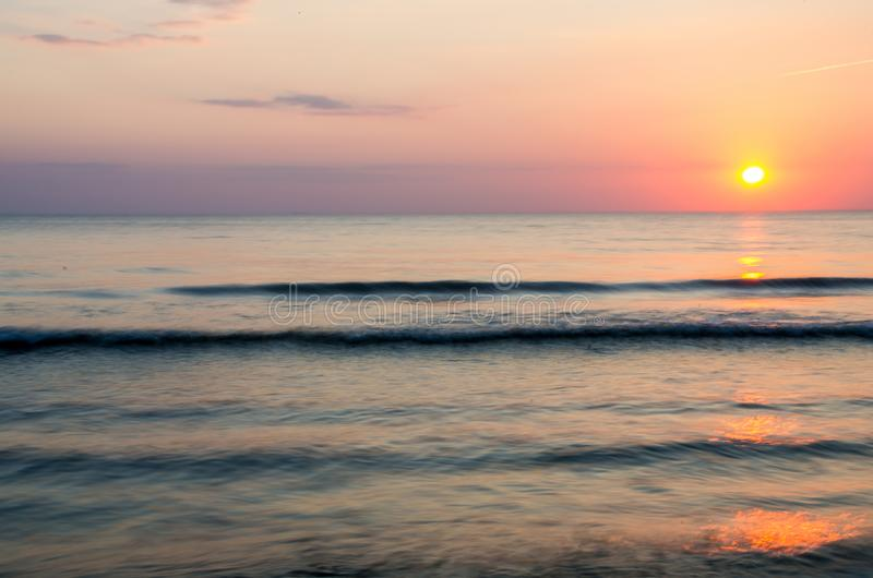 Beautiful sunrise and sunset with clouds over horizon blue sea background in morning and evening. Scenic seascape with golden stock image