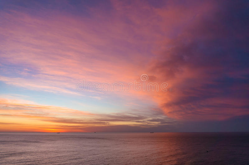 Beautiful sunrise, sunset sky over calm ocean. Seascape with amazing pink clouds royalty free stock images