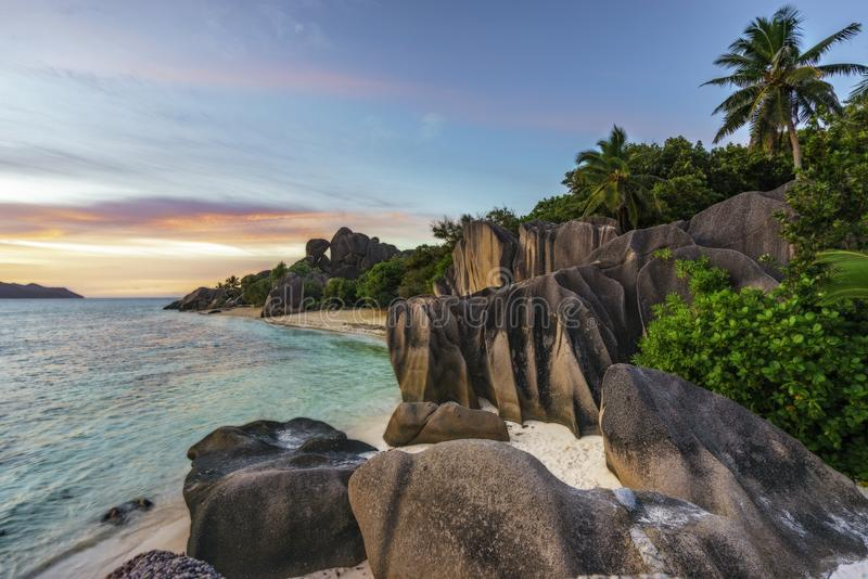 sunset over rocks,sand,palms,turquoise water at tropical beach,la dique,seychelles paradise 1 stock photos