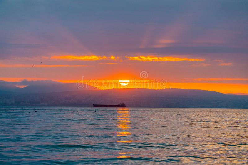 Beautiful sunset amongst the clouds. The sun rays are simply beautiful. City, mountains and ships in sea stock image
