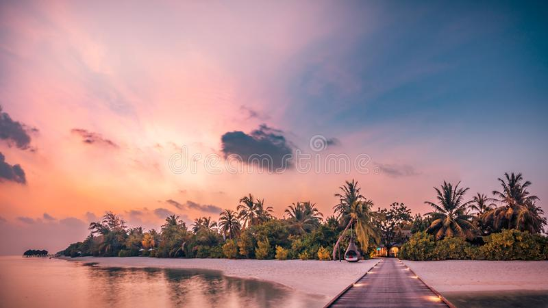 Beautiful sunset beach scene. Colorful sky and clouds view with calm sea and relaxing tropical mood royalty free stock photo