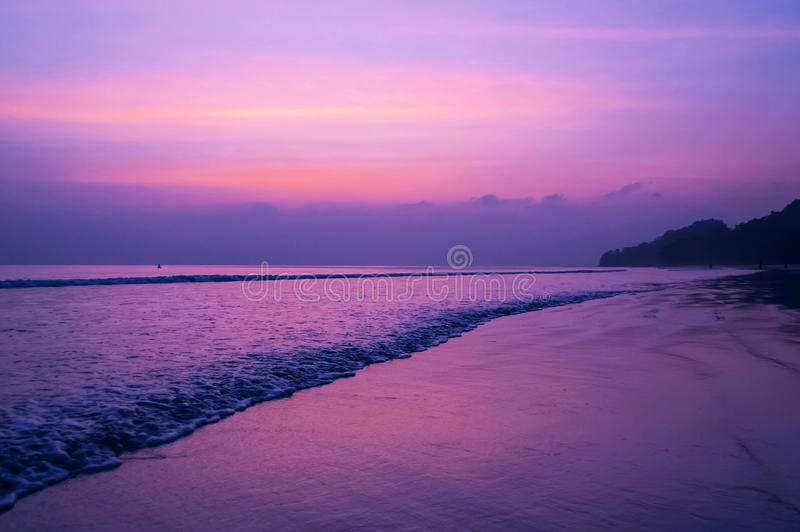 Beautiful sunset beach with sweet purple orange blue sky. And clouds, people or tourist walk on beach in the evening very peaceful royalty free stock photos