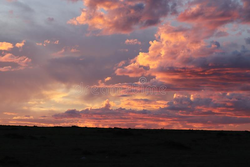 Beautiful sunset and clouds in the african savannah. Beautiful pink sunset and clouds photographed in the Maasai Mara National Reserve, in Kenya stock images