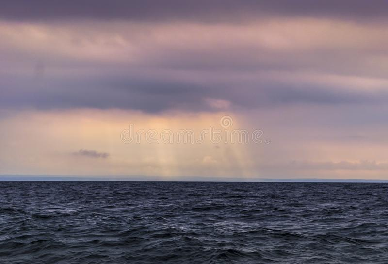 Beautiful sunset through the clouds over the sea.  stock photos