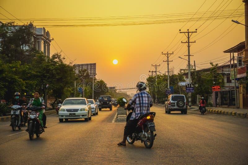 Mandalay, Myanmar - March 26, 2017: Beautiful sunset and evening traffic on the roads of Mandalay. Beautiful sunset and evening traffic on the roads of Mandalay royalty free stock photography