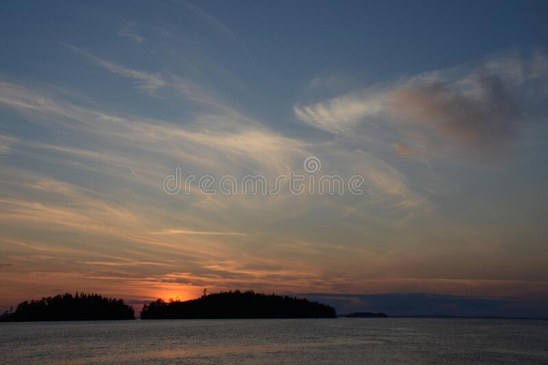 Beautiful sunset on lake and islands. The sun hid behind the islands covered with forest. Cirrus, white clouds over the lake. Beautiful sunset on the lake and royalty free stock image