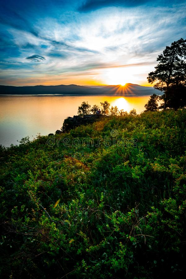 Beautiful sunset landscape on mountain lake with sun hiding behind the mountains. On the opposite bank, russia, sky, clouds, rocks, stone, countryside, forest royalty free stock photos