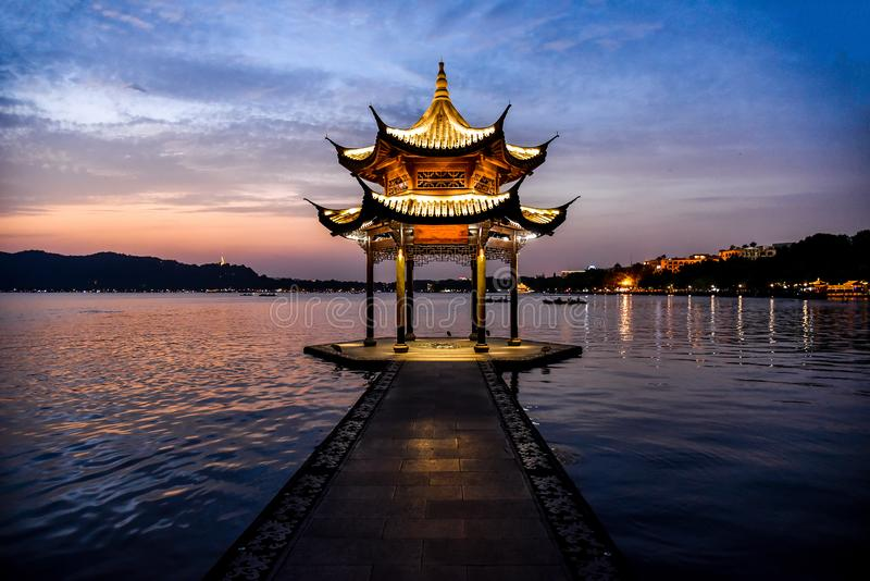 The beautiful Sunset landscape scenery of Xihu West Lake and pavilion with boat and mountain in Hangzhou China.  royalty free stock photography