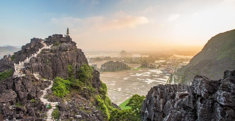 Beautiful sunset landscape viewpoint with white stupa from the top of Mua Cave mountain, Ninh Binh, Tam Coc, Vietnam. Beautiful sunset landscape viewpoint with stock photos