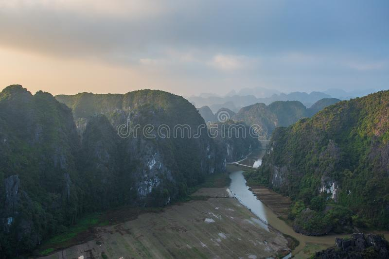 Beautiful sunset landscape viewpoint with white stupa from the top of Mua Cave mountain, Ninh Binh, Tam Coc, Vietnam. Beautiful sunset landscape viewpoint with stock images
