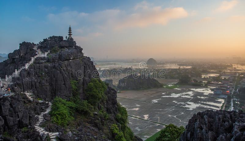 Beautiful sunset landscape viewpoint with white stupa from the top of Mua Cave mountain, Ninh Binh, Tam Coc, Vietnam. Beautiful sunset landscape viewpoint with stock photography