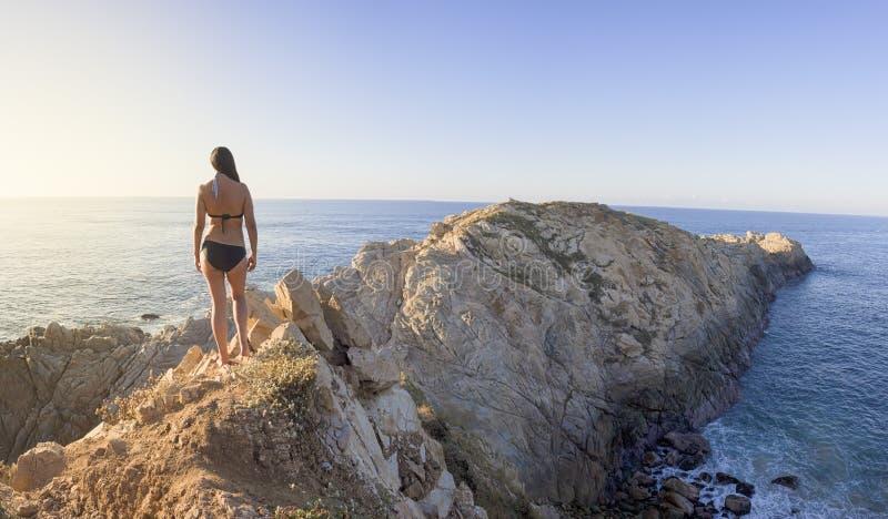Beautiful sunset, latin woman, panoramic view, comet point, huatulco Mexico. Agua, america, azul, beach, blue, bush, cliff, coast, coastline, colorful, empty stock photos