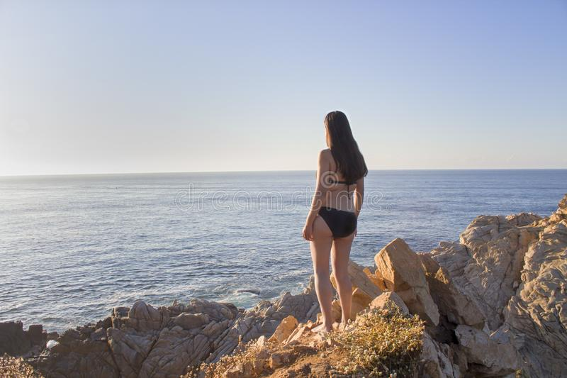 Beautiful sunset, latin woman, panoramic view, comet point, huatulco Mexico. Agua, america, azul, beach, blue, bush, cliff, coast, coastline, colorful, empty royalty free stock photography