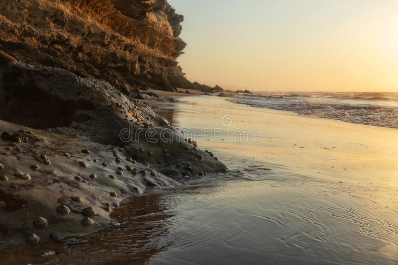 Beautiful sunset on the Namibe wild beach, Africa. Angola. With cliff and rocks royalty free stock image