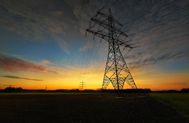 Beautiful Sunset next to powerlines. This is a picture of a powerline next to munich. It is a well thought composition, which is really pleasant to your eyes royalty free stock photography