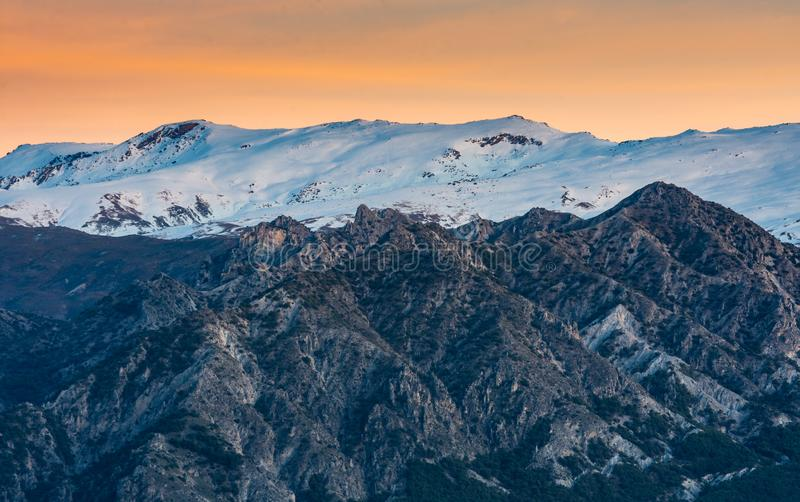Beautiful sunset with orange tones in the sky and Sierra Nevada snowcapped mountain range. In the south of Spain, Granada royalty free stock images