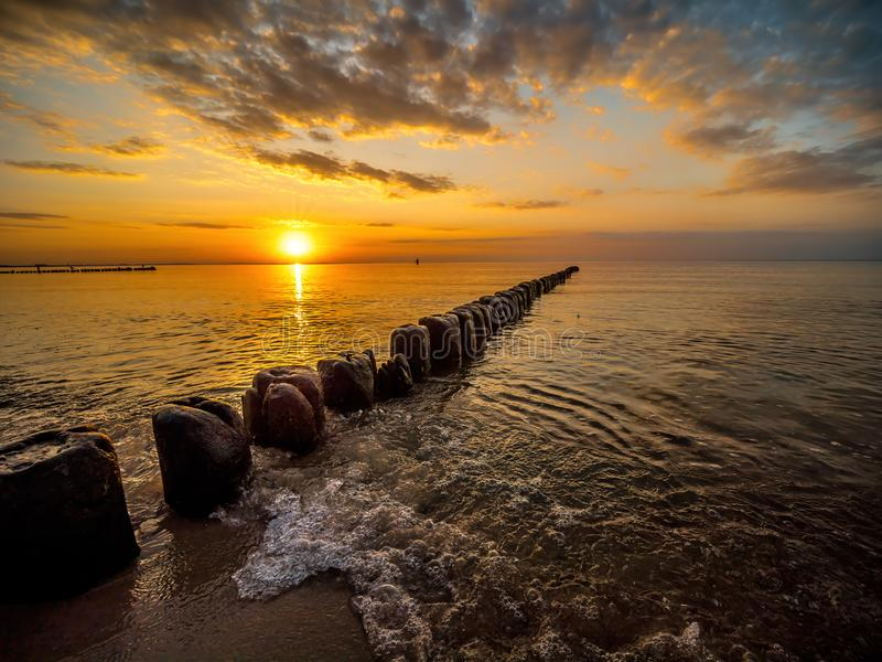 Old wooden wave breakers against the sunset stock photos
