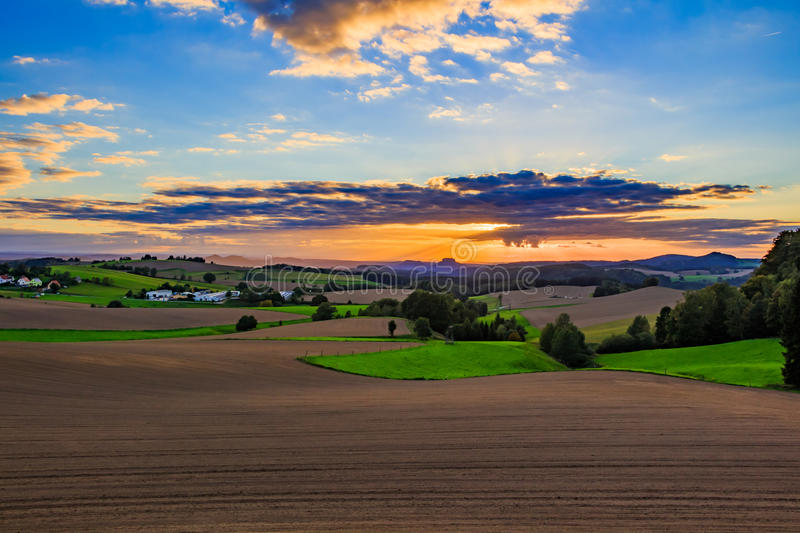 Beautiful sunset over countryside landscape of rolling hills with sun beams piercing sky and lighting hillside.  royalty free stock photos