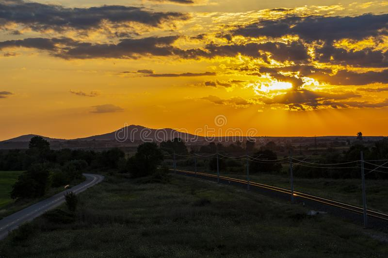 Beautiful sunset over empty railway tracks. Beautiful summer sunset over sunlit empty railway tracks and an asphalt road near Krum, Southern Bulgaria, elevated stock image