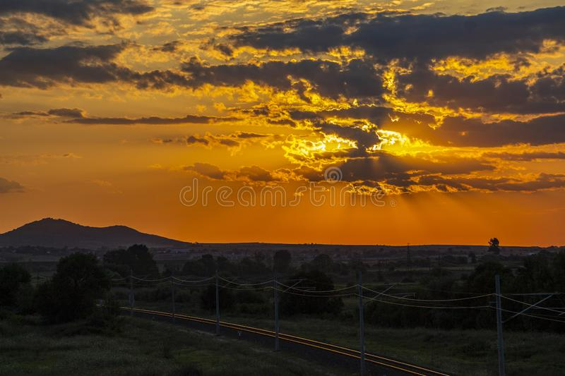 Beautiful sunset over empty railway tracks. Beautiful summer sunset over sunlit empty railway tracks near Krum, Southern Bulgaria, elevated view from a bridge stock photo