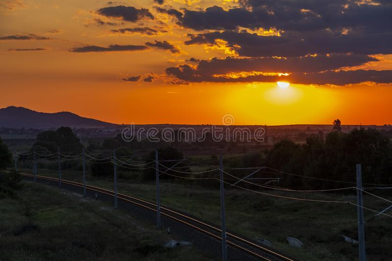 Beautiful sunset over empty railway tracks. Beautiful summer sunset over empty sunlit railway tracks near Krum, Southern Bulgaria, elevated view from a bridge stock photo