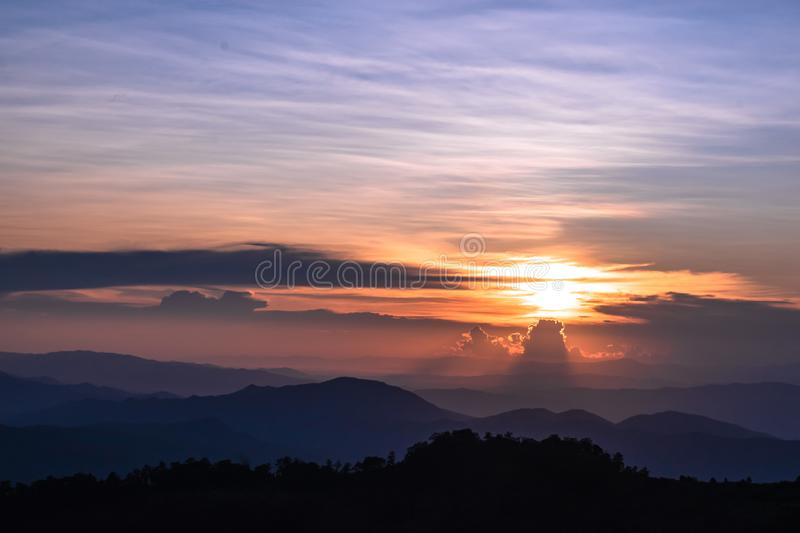Beautiful sunset over the mountains, landscape of Phu Soi Sao, Nampad, Uttaradit province northern of Thailand. Silhouette of pine trees, landscape of phu soi stock photo