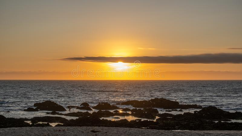 Beautiful sunset over ocean with bright orange sky and shining sun behind cloud on horizon. Beautiful sunset over ocean with bright orange sky and shining sun royalty free stock images