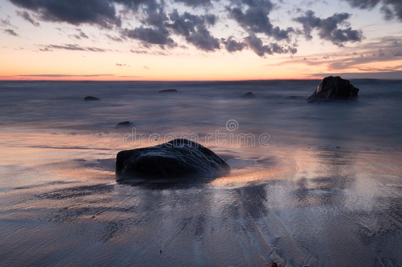 Beautiful sunset over ocean with rocks and reflections in the water royalty free stock image